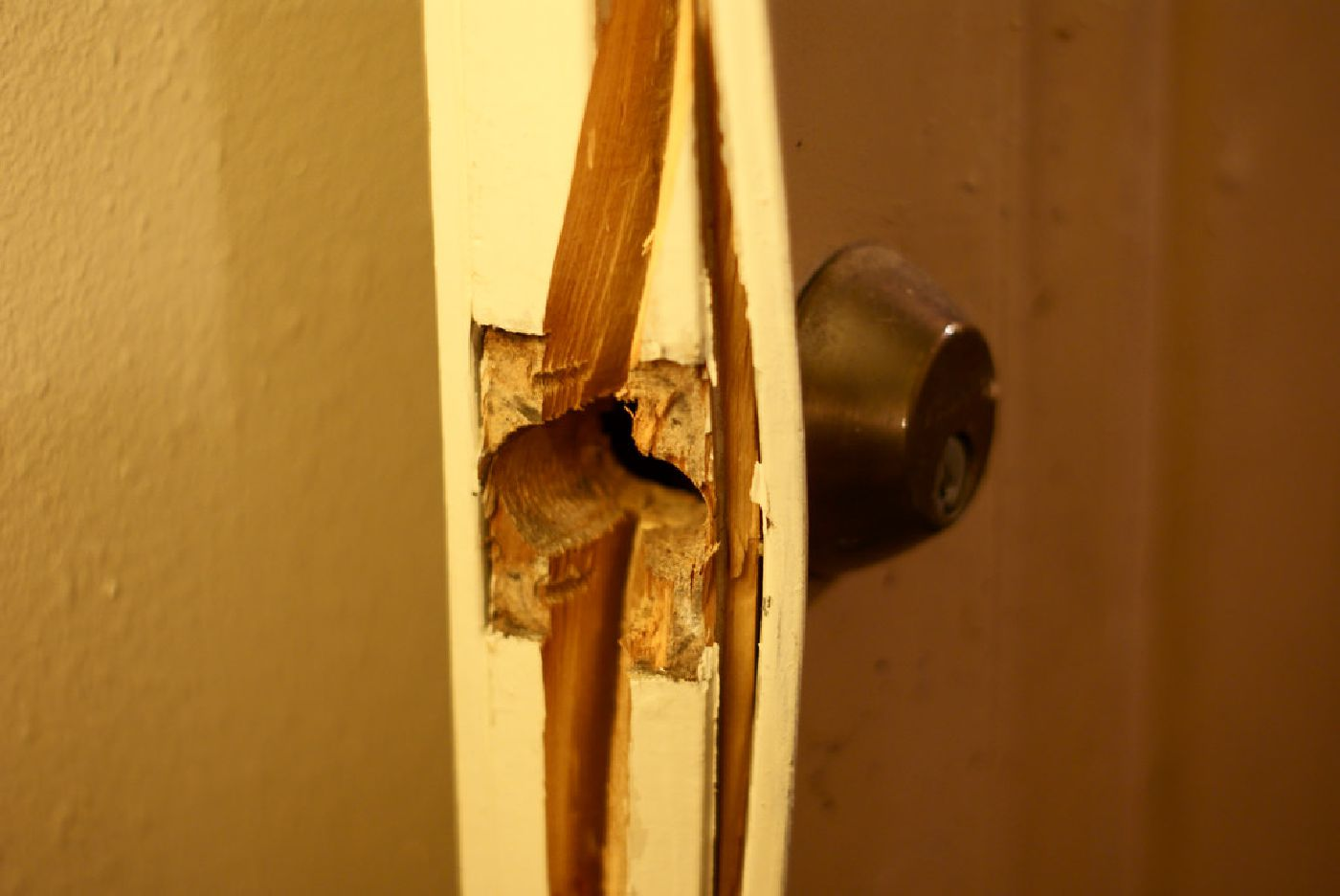 Close-up of a regular door split apart by a forceful kick