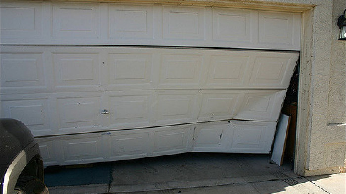 Image of an overhead roll-up garage door pushed in by a car gaining access