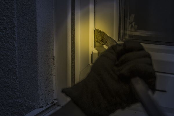 Image of a burglar prying open a window at night